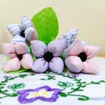Tekstylne kwiaty jako dekoracja stołu przy uroczystym posiłku. Dobry upominek dla najbliższych.